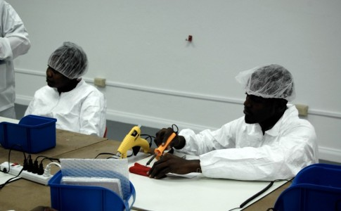 Surtab workers in manufacturing plant soldering together Surtab electronic components